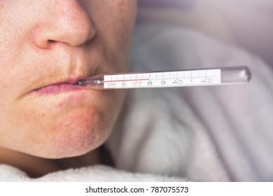Femme malade dont la grippe saisonnière mesure la température corporelle avec un thermomètre dans la bouche atteignant 38 degrés celsius