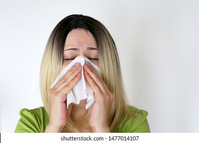 Sick woman sneezing in a handkerchief. Blonde girl with eyes closed on white background, concept of colds and flu, runny nose, airborne infection, nosebleed