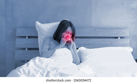 Sick Woman sneezing into Tissue on the bed