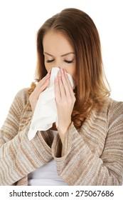 Sick woman sneezing into tissue.