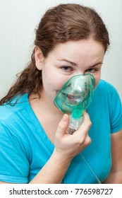 Sick woman with sore throat making inhalation itself with a mask on her face. Nebulizer device