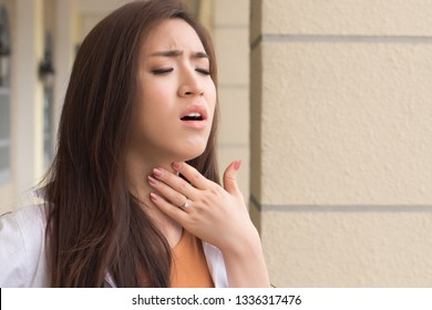 sick woman with sore throat; portrait of woman suffering from cold, flu, sickness with sore throat inflammation; female body care, sickness, allergy, pain concept; asian 20s young adult woman model