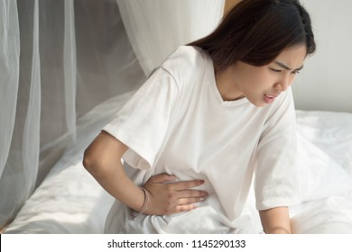 sick woman with stomachache or period cramp; portrait of woman suffering from stomach ache, period cramp, indigestion, food poisoning, flatulence, woman health care concept; asian adult woman model