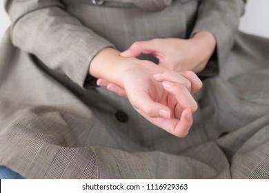 sick woman with trigger finger pain; portrait of sick asian woman suffering from trigger finger, cps, wrist joint pain, arthritis, gout, gouty pain health care concept; asian young adult woman model