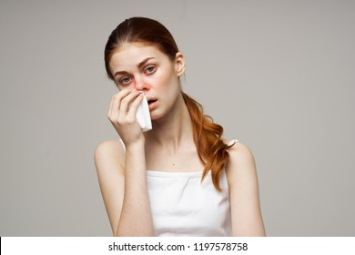 sick woman wipes a red nose with a handkerchief