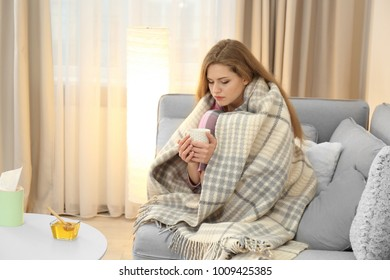 Sick woman wrapped in warm blanket at home. Bowl of honey on table near her