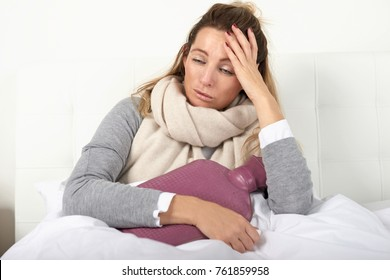 Sick woman wrapped in a warm scarf and clutching a hot water bottle sitting using nasal spray with a miserable expression in a seasonal healthcare or flu concept