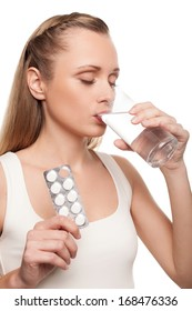 Sick woman. Young woman taking pills and keeping eyes closed while standing isolated on white
