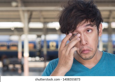 sick young adult man suffering from dry eye, eye irritation or inflammation