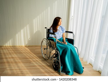 The Sick young asian woman 25 years old sitting in a wheelchair feels hopeless near window. A 25s ill asian woman sitting a wheelchair in hospital