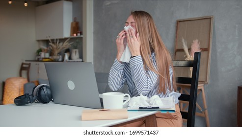 Sick young beautiful Caucasian woman coughs and sneezes with tissues, using laptop to work from home on quarantine.