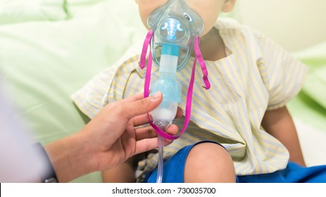 Sick young boy, 3 years old, inhale medication by inhalation mask to cure Respiratory Syncytial Virus (RSV) on hospital bed.