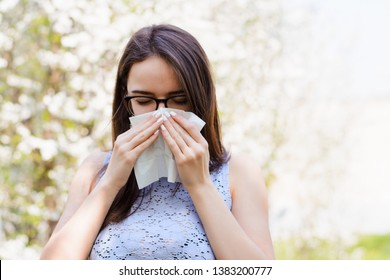 Sick young girl against blooming trees in spring. Outdoor shot of irritated female with seasonal allergy, uses white tissue, poses in light blouse with napkin, has rhinitis and sneezing