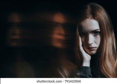Sick young girl with bipolar disorder against black background with blurred person