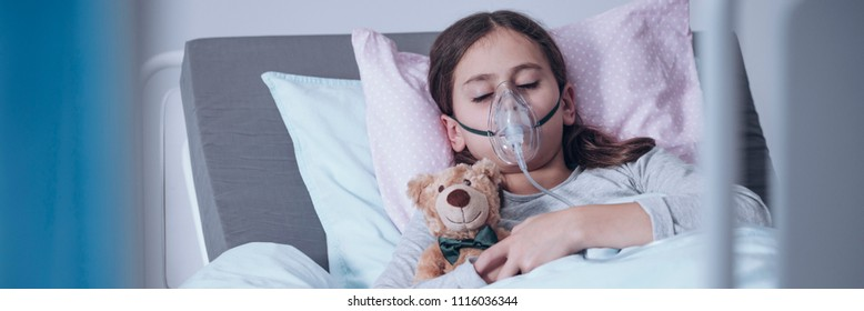 Sick young girl in a hospital bed sleeping with an oxygen mask and a toy, getting treatment for cystic fibrosis