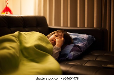 Sick Young Japanese Girl resting on a Sofa.