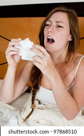 A sick young lady in bed, holding a tissue in front of her face to stop a sneeze.