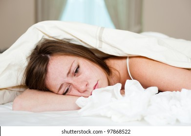 A sick young lady in bed, lying with her head under the blankets and a pile of tissues in front of her.