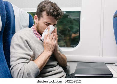 sick young man blowing his nose sitting in the train