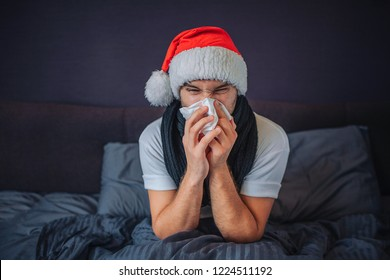 Sick young man in christmas red hat sits on bed. He is covered with blanket. Guy sneezing into tissue. He suffers. Young man feels terrible. He is concentrated on sneezing.
