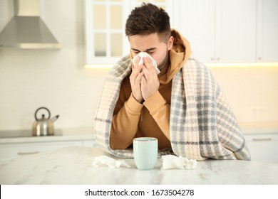 Sick young man with cup of hot drink and tissues in kitchen. Influenza virus