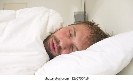 sick young man with fever asleep in bed, covered by a blanket
