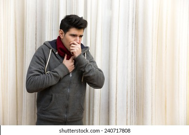 Sick young man with flu or cold, coughing with hand on his mouth. Indoor shot at home