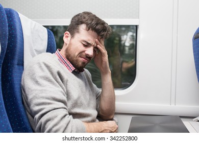 sick young man having a headache sitting in the train