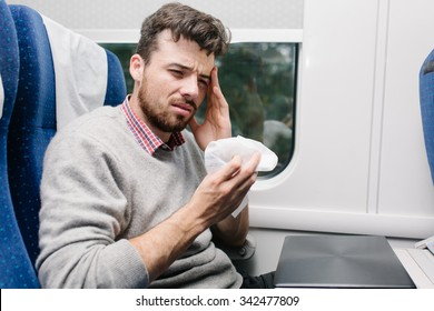 sick young man having a headache sitting in the train and holding a tissue