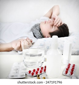 Sick Young Man sleeps with Pills on foreground Focus on the Pills
