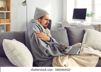 Sick young man wrapped in blanket sitting on sofa with laptop in living-room, having fever and chills, shivering, listening to online doctor's consultation or looking for information on flu virus
