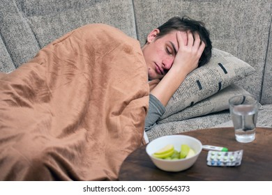 Sick Young Man.Flu.Man Caught Cold. Headache. Virus .Medicines. A sick young man lying on a bed, concept of healing, headache, illness, flu, hangover, abdominal pain.
