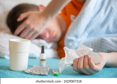 Sick Young Man.Flu.Man Caught Cold. Headache. Virus .Medicines. A sick young man lying on a bed, concept of healing, headache, illness, flu, hangover, abdominal pain. Abstract.