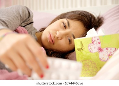 sick young woman in bed feeling pain