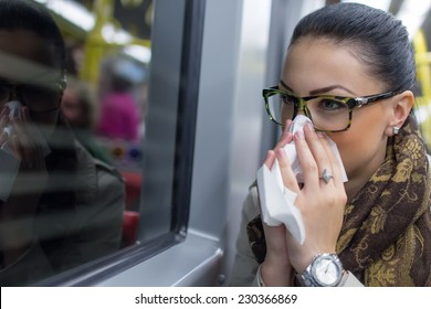 Sick young woman blowing her nose with handkerchief