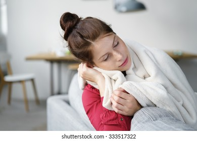 Sick Young Woman Covered with Blanket Sitting at the Couch In the Living Room.