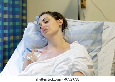 Sick young woman laying in hospital bed with Central Venous Catheter (CVC) being administered fluids and Parenteral Nutrition (PN)