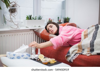 Sick young woman laying in sofa at home and takes white tissue
