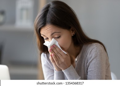 Sick young woman sitting indoors holding tissue handkerchief blowing running nose feels unwell unhealthy, girl having symptoms of chronic sinusitis disease, seasonal allergy or cold fever flu concept