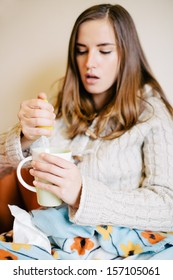 Sick young woman squeezing lemon in tea