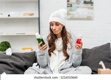 sick young woman in warm clothes choosing between red and green bottles of gargling liquids at home