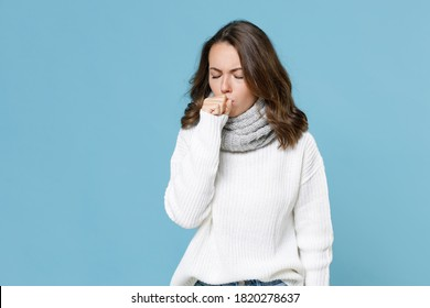 Sick young woman in white sweater gray scarf coughing covering mouth with hand keeping eyes closed isolated on blue background studio. Healthy lifestyle ill sick disease treatment cold season concept - Shutterstock ID 1820278637