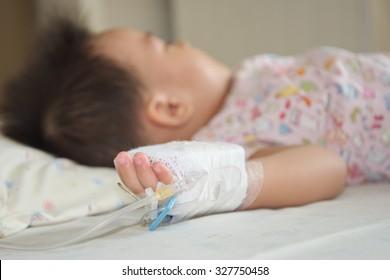 Sicked kid sleeping in hospita,Illness little asian (thai) baby asleep on a sickbed, saline intravenous on hand