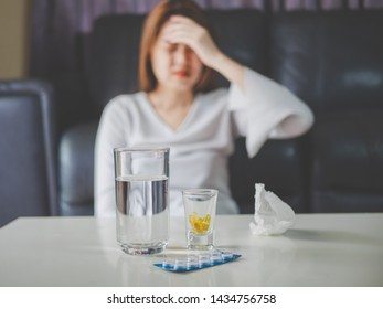sickness and gynecology concept from abstract blurred of woman with allergy, feeling dizzy and fever sit at sofa in home. focus at pills and glass of water on the table.