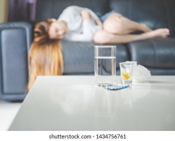 sickness and gynecology concept from abstract blurred of woman with allergy, feeling dizzy and fever sleep on sofa in home. focus at pills and glass of water on the table.