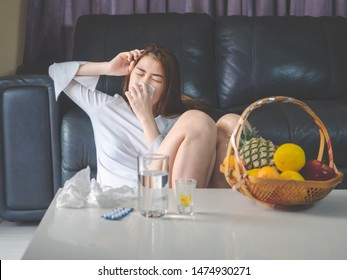 sickness and gynecology concept from woman with allergy, feeling dizzy, sneeze and fever sit at sofa in home, have pills and glass of water laying the table.