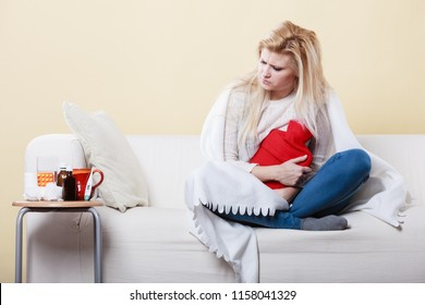 Sickness, seasonal virus problem concept. Woman being sick having flu lying on sofa hugging hot water bottle