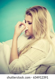 Sickness, seasonal virus problem concept. Woman being sick having flu lying on sofa sneezing into tissue