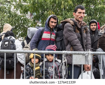 SID, SERBIA - NOVEMBER 17, 2015: Refugees, men and children standing and waiting to cross the Croatia Serbia border, at the Sid train station on the Balkans Route, during the Refugee Crisis
