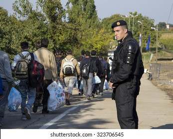 SID, SERBIA - OCTOBER 3, 2015: Croatian policemen watching refugees crossing the Serbo-Croatian border between the cities of Sid (Serbia) and Bapska (Croatia).